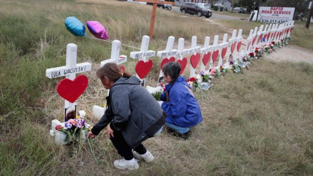 Two women place flowers in memory of victims of a mass shooting.