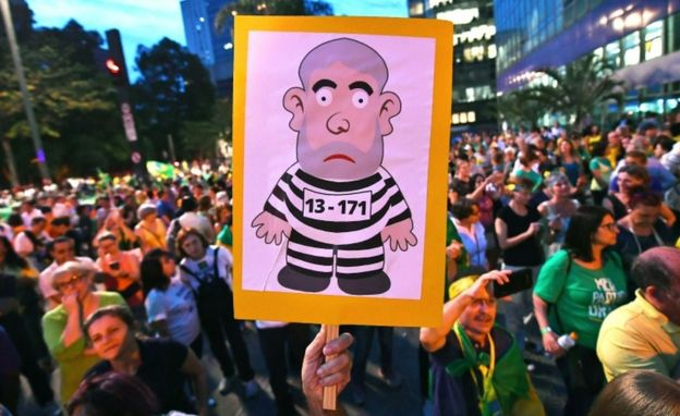 A crowd of anti-Lula demonstrators in Sao Paulo, Brazil. One carries a placard with a picture of a cartoon robber.