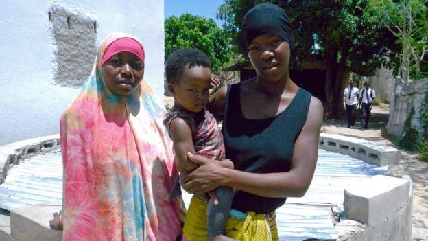 Anchia, 21 anos, com a filha no colo, ao lado de uma amiga, em frente ao reservatório de água da vizinha