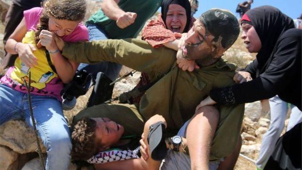 Ahed Tamimi (a la izquierda) muerde a un soldado israelí que trataba de detener a su hermano (28/08/15)