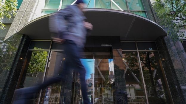 A pedestrian runs past the building where Japan's Coincheck Inc company is located in Tokyo, Japan, 27 January 2018