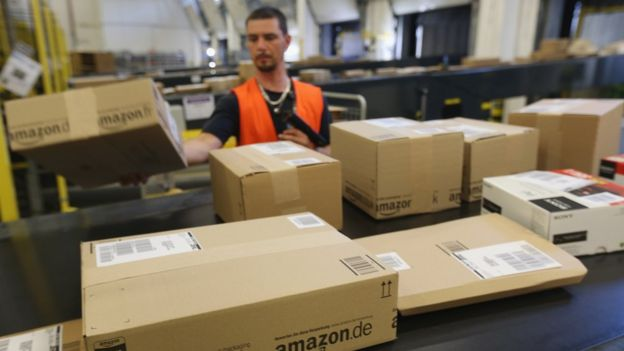A worker prepares packages for delivery at an Amazon warehouse on September 4, 2014 in Brieselang, Germany.