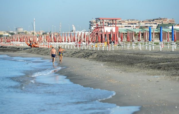 An elderly couple strolls along the shore at Lido di Ostia, near Rome, on August 3, 2012. (Photo: Andrea Solaro)