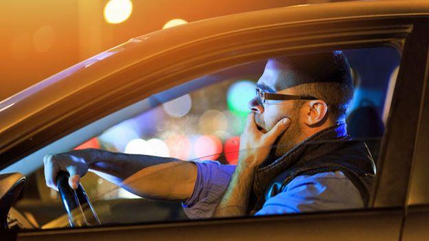 Hombre somnoliento manejando un vehículo.