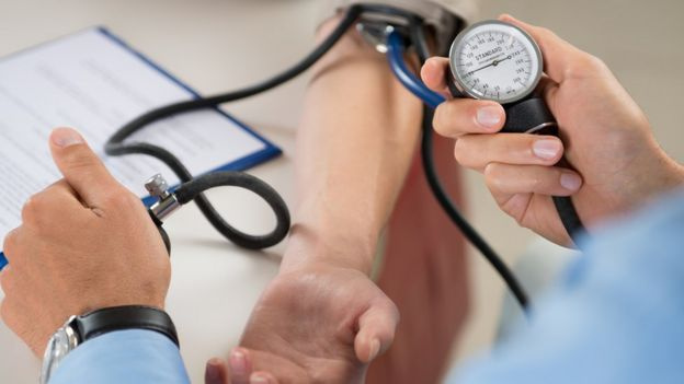 Cardiologist takes blood pressure
