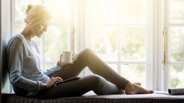 Una mujer sentada en el borde de una ventana