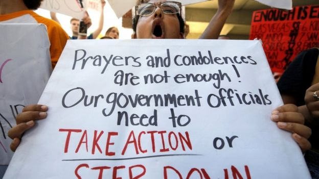 "A student holds a sign saying ""prayers and condolences aren't enough! Our government officials need to take action or step down"""
