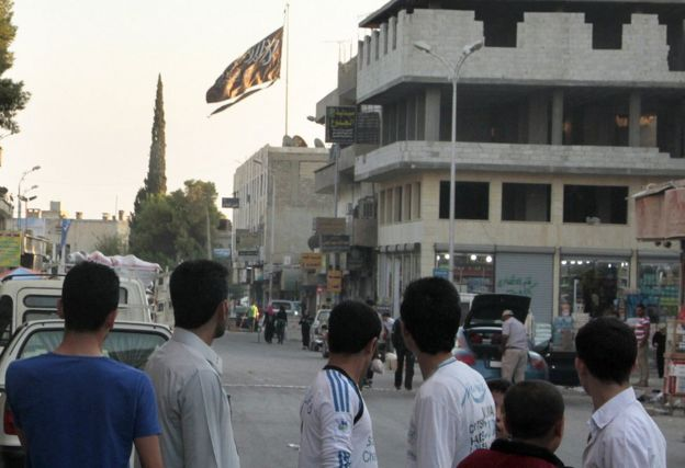 "A group of men look at a large black jihadist flag with Islamic writing on it proclaiming, ""There is no God but God, and Mohammed is the prophet of God""."