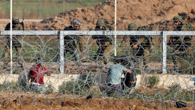 Israeli soldiers arrest three Palestinians who approached the Gaza-Israel border fence during a protest on 15 May 2018