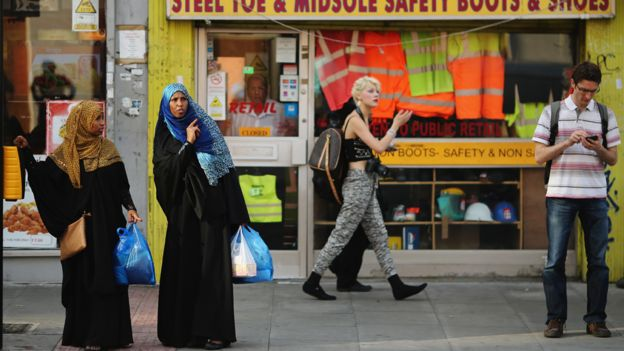 women wait to cross a road in London