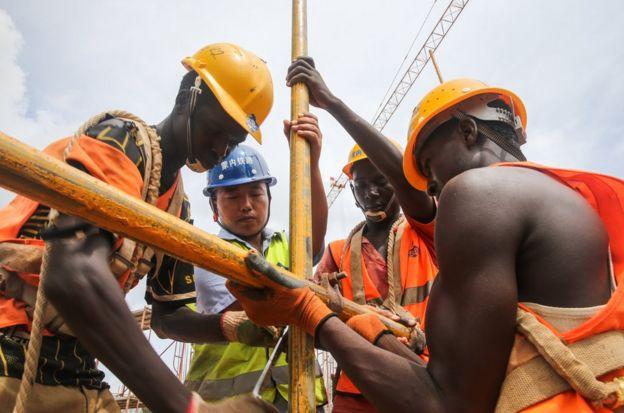 2016年4月9日,中国工程师张青春(左二)和肯方工人在在肯尼亚蒙内铁路蒙巴萨西站工地上工作(资料照片)。