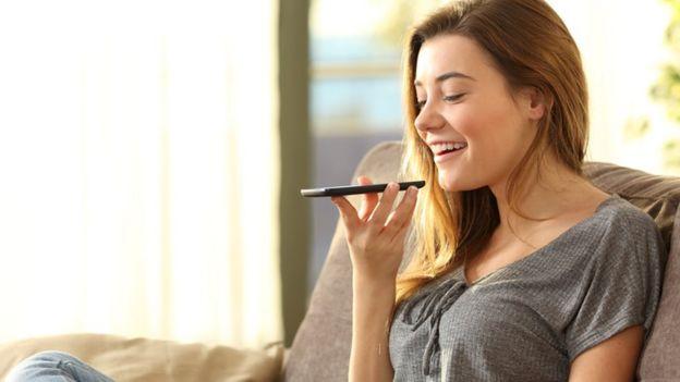 Una mujer utiliza la herramienta de reconocimiento de voz en su celular.