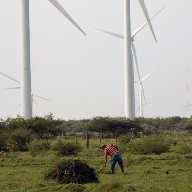 Un hombre trabaja la tierra junto a un campo eólico en Juchitán, Oaxaca, México.