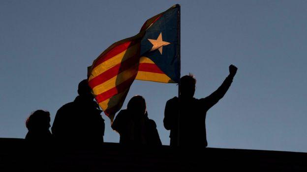 Manifestantes en Barcelona elevando la bandera de Cataluña.