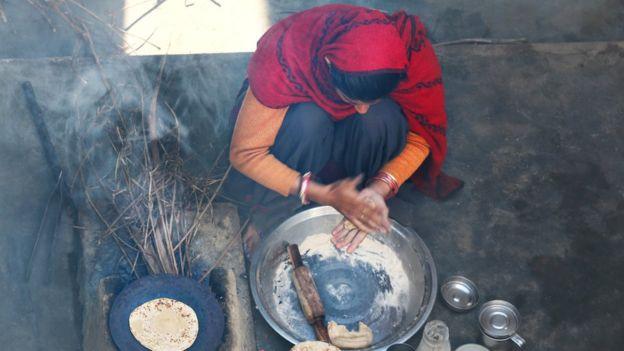 Mujer de país en desarrollo cocinando.
