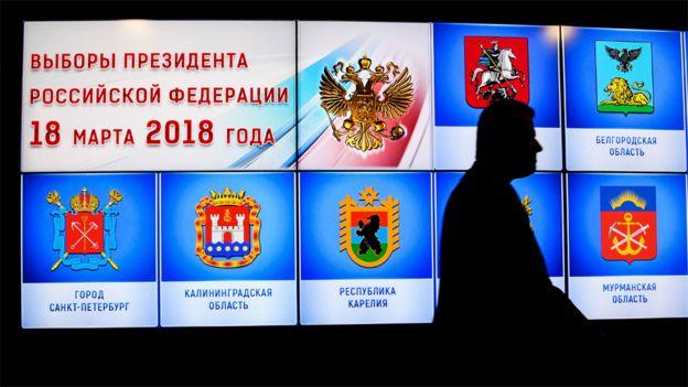Un hombre pasa frente a una pantalla que anuncia la elección y en la que se ven los escudos de armas de las distintas regiones de Rusia.
