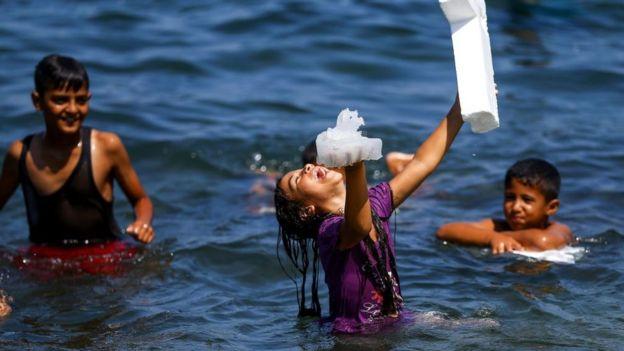 Gazzeli bir kız bir elinde denizanası, diğer elinde kçpükle suda oynuyor