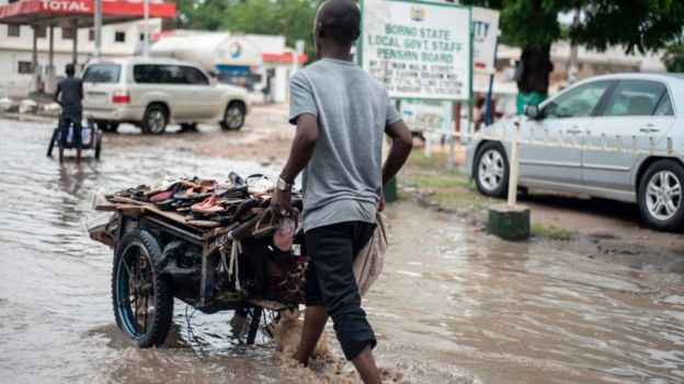 A sandal vendor pushes his cart through the flooded streets of Maiduguri in north-east Nigeria on July 5, 2017.
