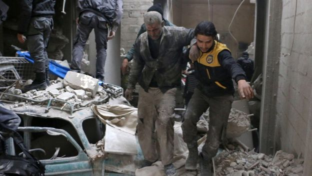 Rescue workers evacuate a wounded civilian from the site of a reported government air strike in Douma, in the besieged rebel-held Eastern Ghouta, Syria (22 February 2018)