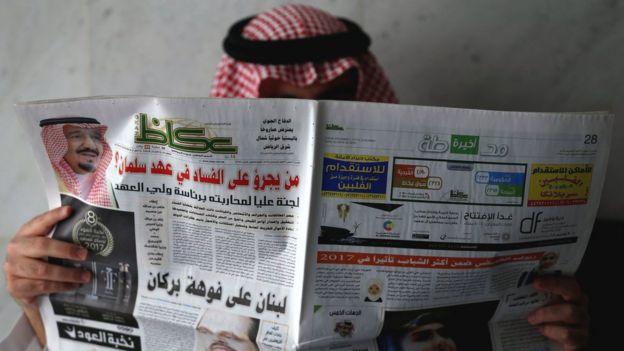 Un hombre saudita lee un periódico donde se habla de la campaña anticorrupción.