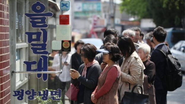 "People wait in a long queue to enter a restaurant famous for Pyongyang-style cold noodles, or ""naengmyeon"" in Korean, in Seoul, South Korea, 27 April 2018"