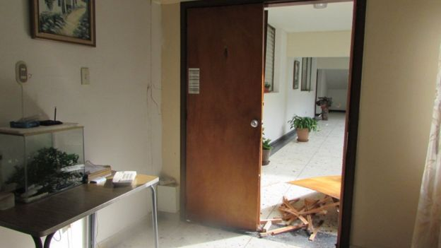 A door lies in pieces at the entrance to a room at the building housing Christian Brothers