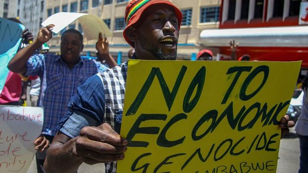 A protester holds a sign during a demonstration by opposition parties against the introduction of bond notes as a currency in Harare on November 30 2016