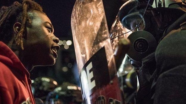 Mujer negra enfrentándose a un policía durante una protesta.