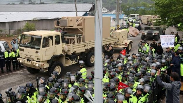 Police and protesters line the road as Thaad equipment is moved into place (26 April 2017)
