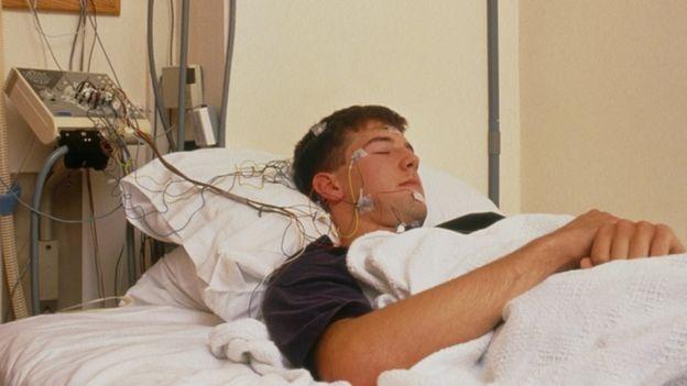 Voluntario durmiendo, con cables conectados a su cabeza