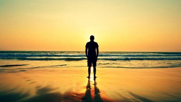 شاب يقف وحيدا أمام شاطئ البحر