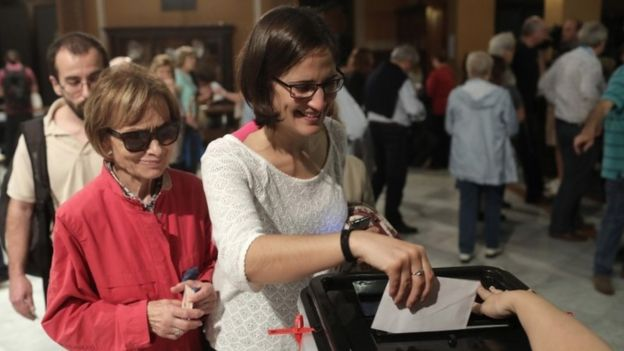 Two women cast their ballot in the referendum vote at Escola Industrial of Barcelona school polling station on October 1, 2017 in Barcelona, Spain