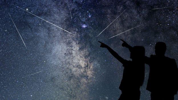 Pareja a oscuras señalando cielos estrellados.