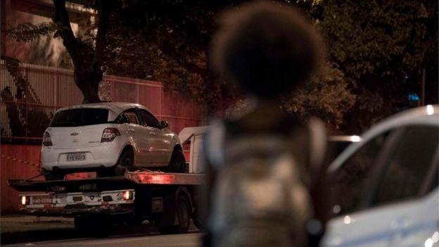 Mulher observa retirada do veículo onde Marielli morreu