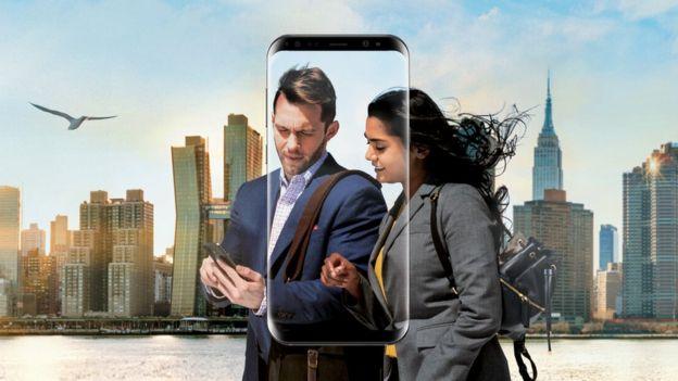 pareja usando un teléfono Samsung con rascacielos en el fondo.