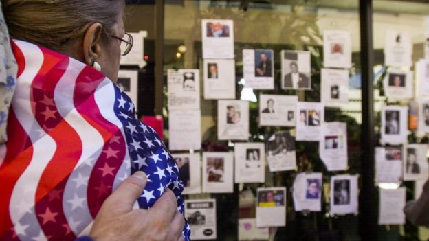 A woman wrapped in the flag of the United States observes a mural with the victims of 11 S