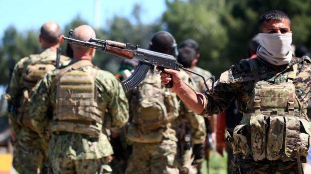 Бойцы курдского ополчения на месте авиаудара, нанесенного турецкими ВВС невдалеке от населенного курдами города Дерик на северо-востоке Сирии 25 апреля