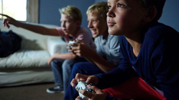 tres niños jugando videojuegos.