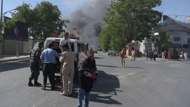 Heridos son trasladados en ambulancia mientras se ve el humo en el fondo.