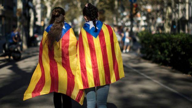 Dos jóvenes caminan por Barcelona envueltas en banderas independentistas de Cataluña.