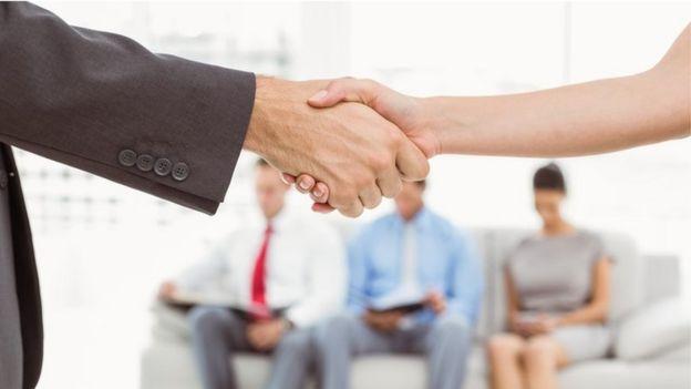Dos personas dándose la mano. Al fondo, tres personas esperan turno para una entrevista de trabajo