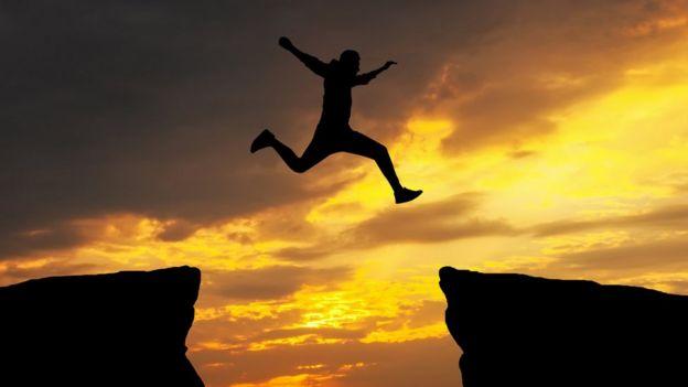 Hombre saltando entre dos precipicios