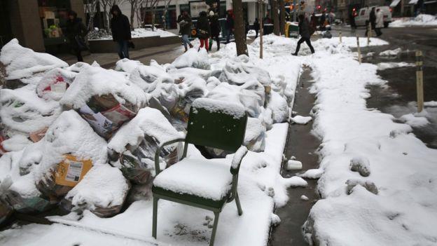 Una silla en medio de una acera llena de nieve en Nueva York