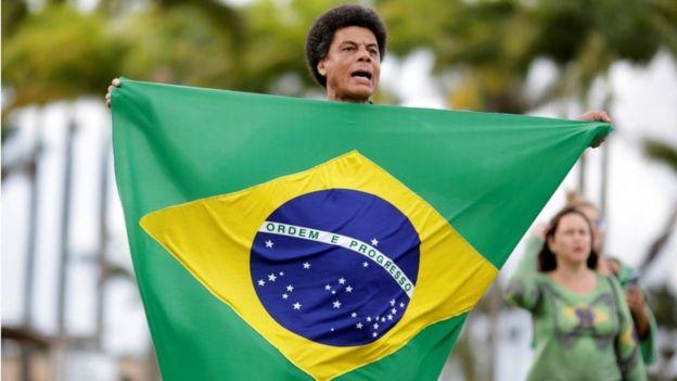 Hombre sostiene una bandera de Brasil.