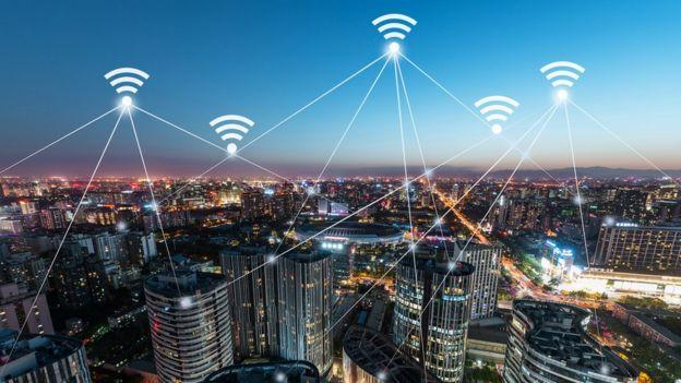Imagem noturna de uma cidade com sinais de Wifi