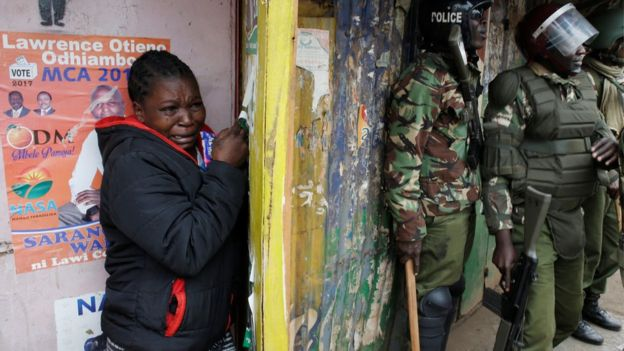 Woman shelters behind police during clashes in Kibera slum