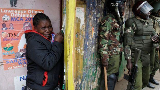 Mwanamke akijikinga Kibera