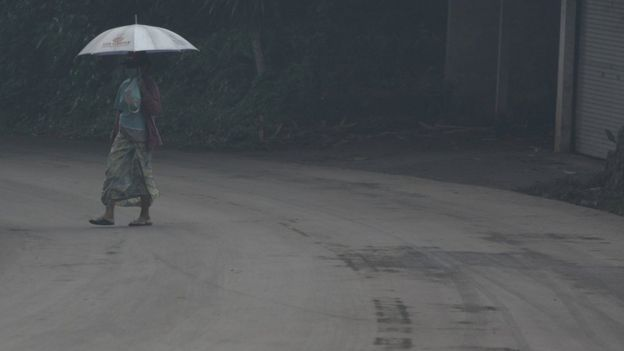 A woman uses an umbrella as she walks through ash from Mount Agung volcano in Bebandem Village, Karangasem, Bali, Indonesia on Sunday. Photo supplied by Antara Foto