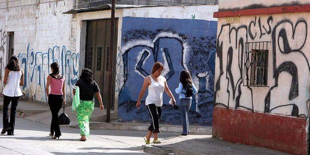 Mujeres en la calle, entre murales de la MS-13