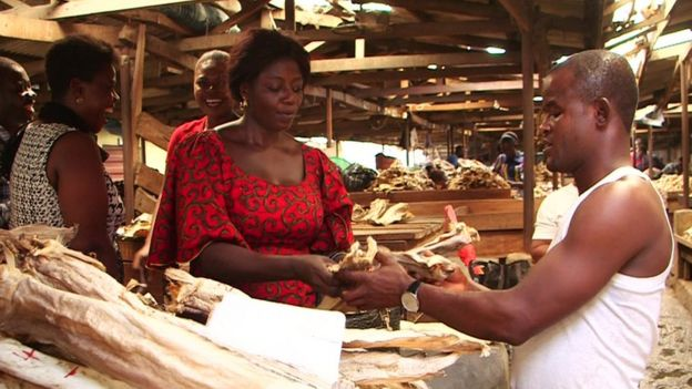 Onyingbo market - a man buys some produce from a woman's wooden stall